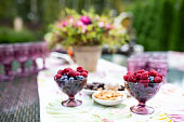 Beautiful glasses of colored purple glass on the table with berries and flowers, composition for catering outdoors