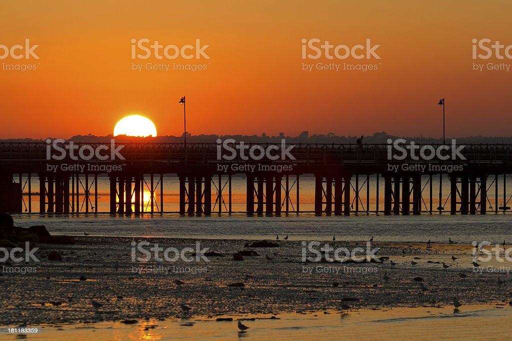 Beautiful glowing sunset behind a pier stock photo