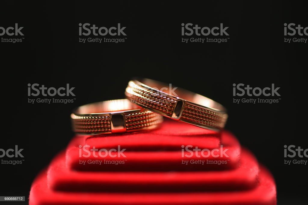 Beautiful gold wedding rings on a red box. Macro photography.