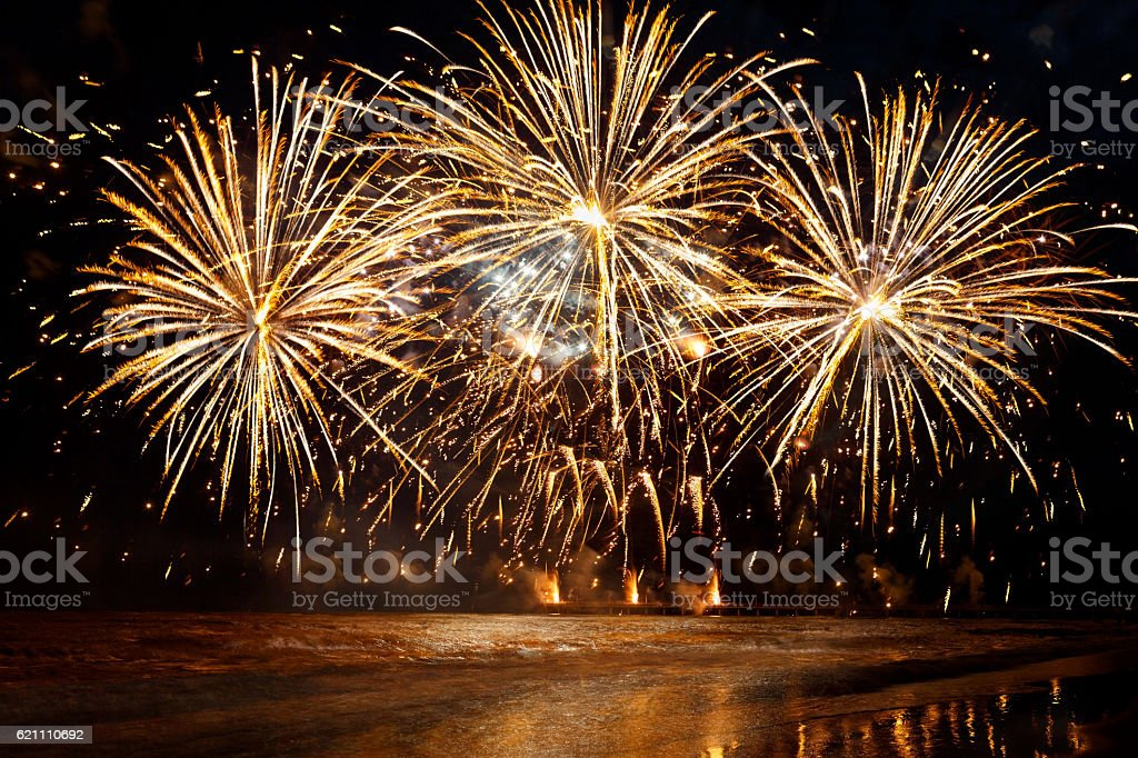 beautiful Golden fireworks over the sea on night sky background stock photo