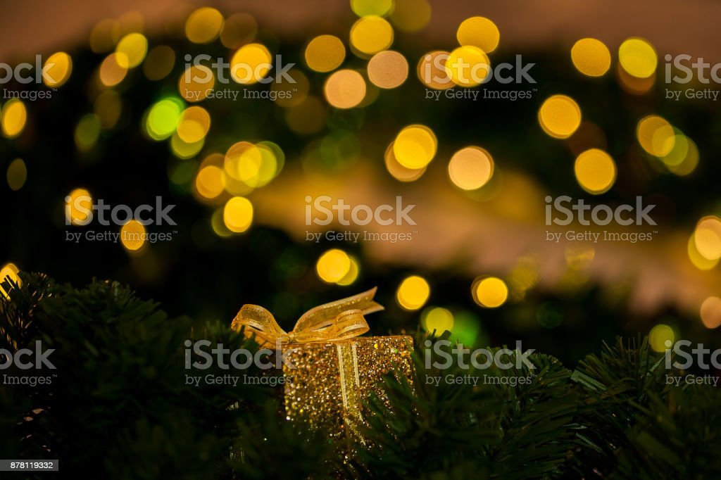 Beautiful golden gift decorated on Christmas tree blurred in gold bokeh background - selective focus. stock photo