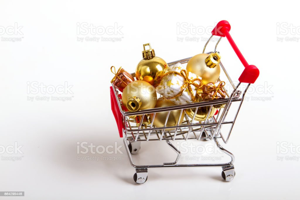 beautiful golden gifts with ribbon and Christmas balls in shopping cart royalty-free stock photo