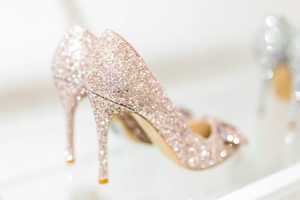 schöne goldene glitter weiblichen schuhen mit hohen absätzen auf glasregal. hochzeits-accessoires. cinderella shoes. selektiven fokus - goldhochzeitsschuhe stock-fotos und bilder