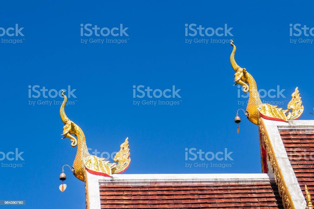Mooie gouden naga beelden op de kerk dak onder de blauwe hemelachtergrond op Wat Phra dat Doi Tung, waarvan er één wordt verondersteld om te bevatten het linker sleutelbeen voor Lord Buddha. - Royalty-free Antiek - Toestand Stockfoto