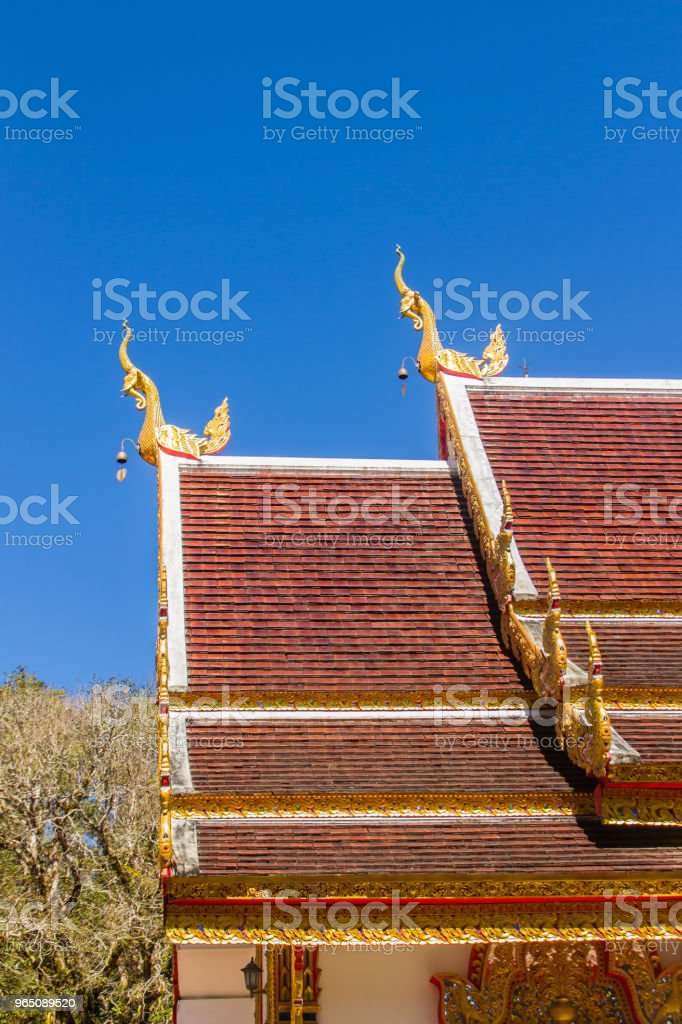 Beautiful golden naga sculptures on the church roof under the blue sky background at Wat Phra That Doi Tung, one of which is believed to contain the left collarbone of Lord Buddha. royalty-free stock photo