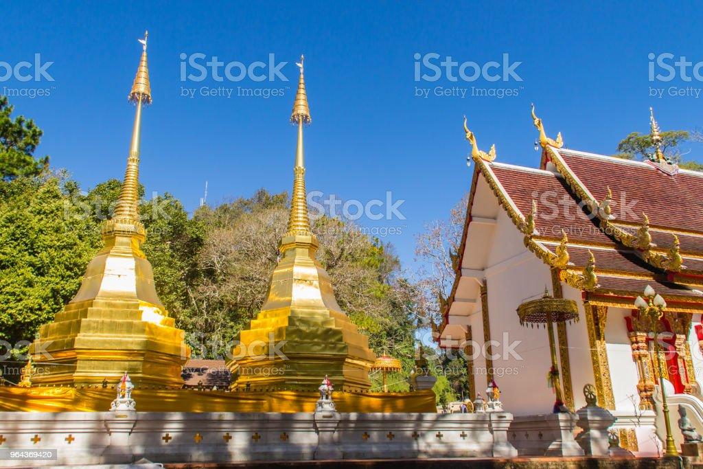 Lindos dourados pagodes em Wat Phra que Doi Tung, Chiang Rai. Wat Phra Doi Tung que compreende de stupas de Lanna-estilo um gêmeo, um dos quais é acreditado para conter a clavícula esquerda do senhor Buddha. - Foto de stock de Amarelo royalty-free