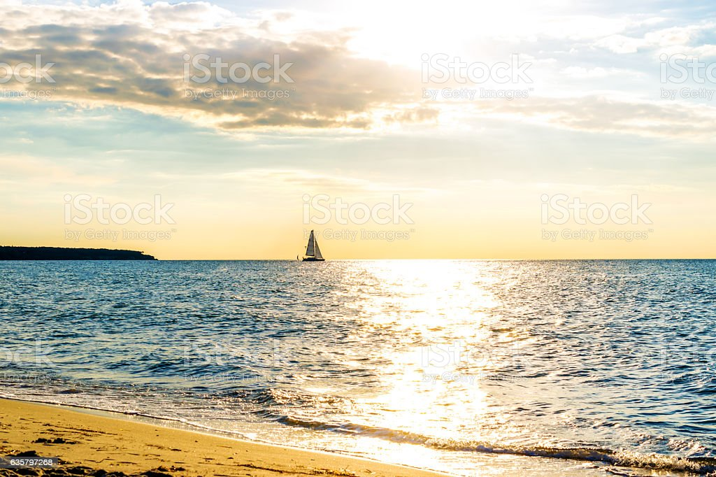 Beautiful golden sundown over the sea with ship on horisont. stock photo