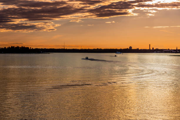 Beautiful golden sunset over lake Vanern in Sweden with city and sky horizon. Ships and small boats. stock photo