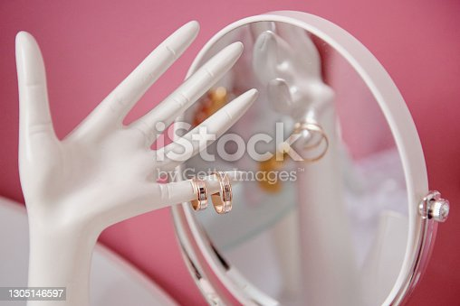 istock Beautiful golden wedding rings on ceramic hand-shaped jewelry holder, copy space. Wedding morning preparation. Bridal accessories, closeup. Marriage concept 1305146597