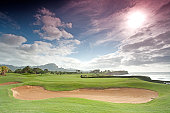 A beautiful golf green and bunker by the sea. Kauai, Hawaii, United States. Golf course scenic. Horizontal colour image with dramatic sky and sun. Golf industry in Kauai is strong with a number of the best golf courses in Hawaii. Nobody is in this image. Sun is masked behind clouds and neutral density grad filter was used for an even exposure. This is one of the best seaside golf holes in the world.
