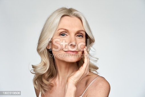 istock Beautiful gorgeous 50s mid aged mature woman looking at camera isolated on white. Mature old lady close up portrait. Healthy face skin care beauty, middle age skincare cosmetics, cosmetology concept 1302319506