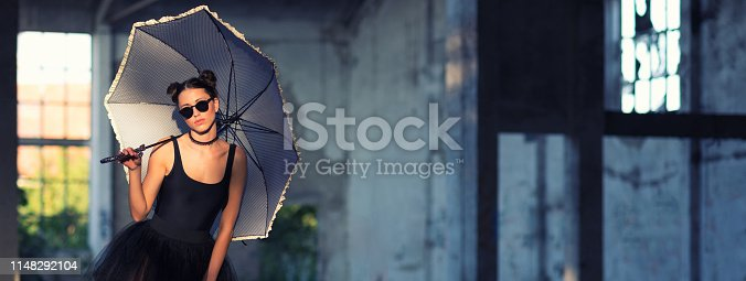 Beautiful goth ballerina standing with umbrella in an abandoned building.
