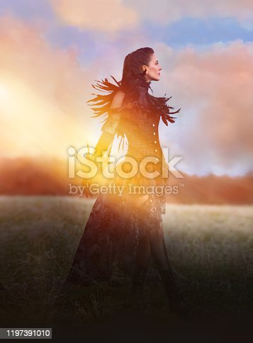 Beautiful goth woman walking in field with fall colors