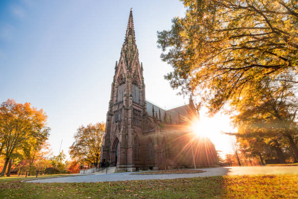 Beautiful Gothic Revival style cathedral at sunset, with golden warm light illuminating the fall foliage around the structure.