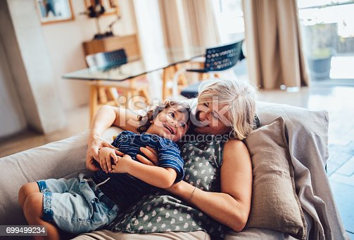 istock Beautiful grandma and grandson playing together having fun at home 699499234