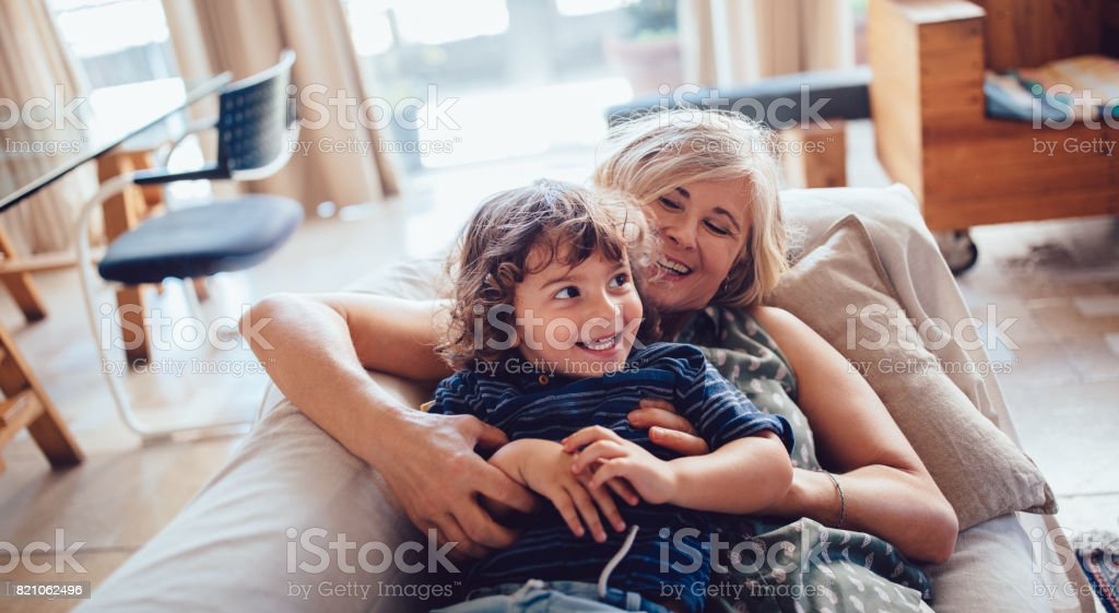 Beautiful grandmother and grandson playing and laughing together stock photo