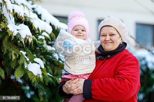 istock Beautiful grandmother holding baby girl in pram during snowfall in winter 917648972