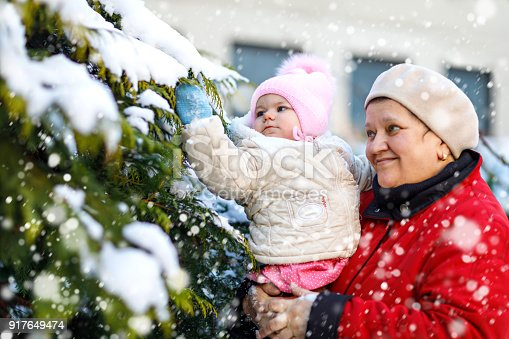 istock Beautiful grandmother holding baby girl in pram during snowfall in winter 917649474