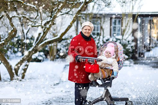 istock Beautiful grandmother walking with baby girl in pram during snowfall in winter 917649888