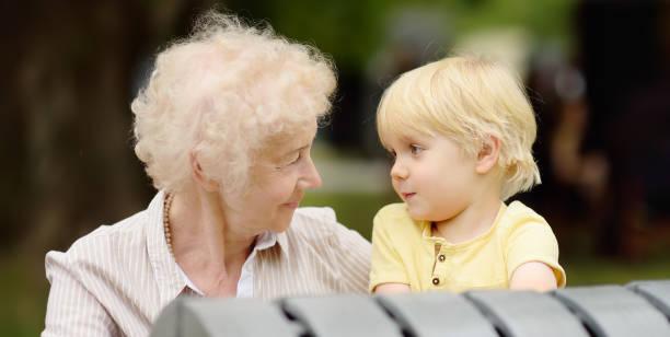 Hermosa abuela y su nieto pequeño juntos caminando - foto de stock