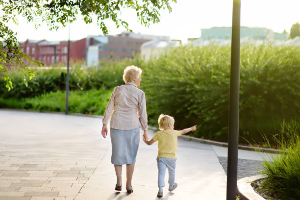 Hermosa abuela y su nieto de poco caminar juntos en el Parque - foto de stock