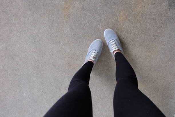 mooie grijze schoenen schoeisel van accessoires. jonge mode vrouw benen in zwarte jeans en grijze sneakers op straat weg achtergrond. - zwarte spijkerbroek stockfoto's en -beelden