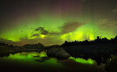 A beautiful green and red aurora dancing over the river Luga, Russia