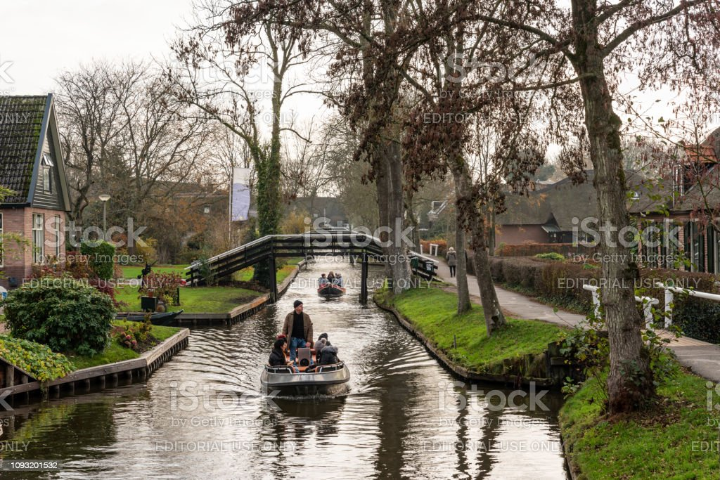 Beautiful green winter scene of people in two small boats cruising on narrow canals among buildings in the famous village Giethoorn Netherlands. stock photo