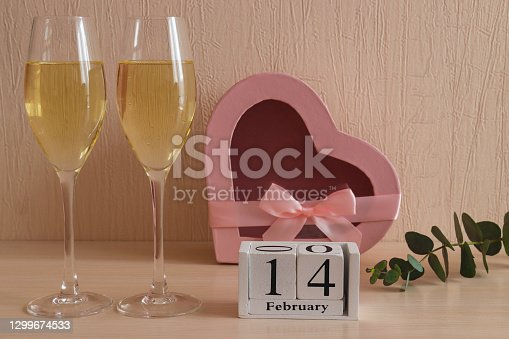 Beautiful greeting card for Valentine's Day. Wooden calendar 14 February, two glasses of champagne and a heart-shaped gift box. Selective focus, close-up.