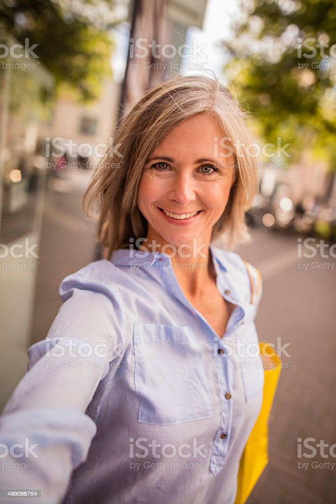 Beautiful grey haired mature woman taking a selfie in town - Stock image .