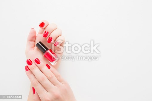 1147741037 istock photo Beautiful groomed woman fingers with red nails on white table background. Young girl hand holding bottle of nail polish. Closeup. Manicure, pedicure beauty salon concept. Empty place for text or logo. 1214200908