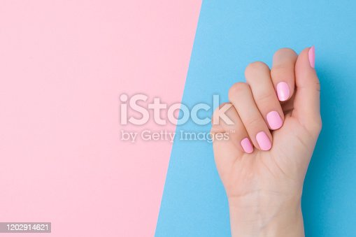 1147741037 istock photo Beautiful groomed woman hand with light pink nails on pastel blue table side. Two colors background. Closeup. Manicure, pedicure beauty salon concept. Empty place for text or logo. Top down view. 1202914621