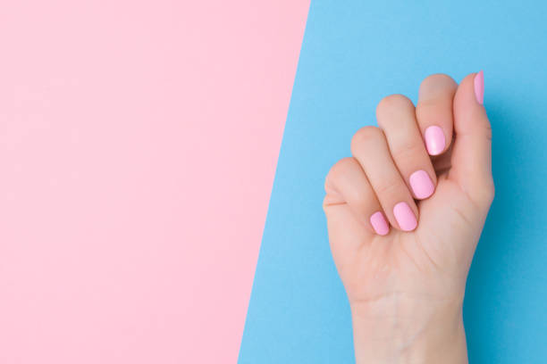 Beautiful groomed woman hand with light pink nails on pastel blue table side. Two colors background. Closeup. Manicure, pedicure beauty salon concept. Empty place for text or logo. Top down view. Beautiful groomed woman hand with light pink nails on pastel blue table side. Two colors background. Closeup. Manicure, pedicure beauty salon concept. Empty place for text or logo. Top down view. pink nail polish stock pictures, royalty-free photos & images