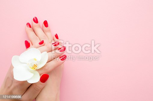 1147741037 istock photo Beautiful groomed woman hands with red nails on pink table background. Pastel color. White orchid flower. Closeup. Manicure, pedicure beauty salon concept. Empty place for text or logo. Top down view. 1214199556