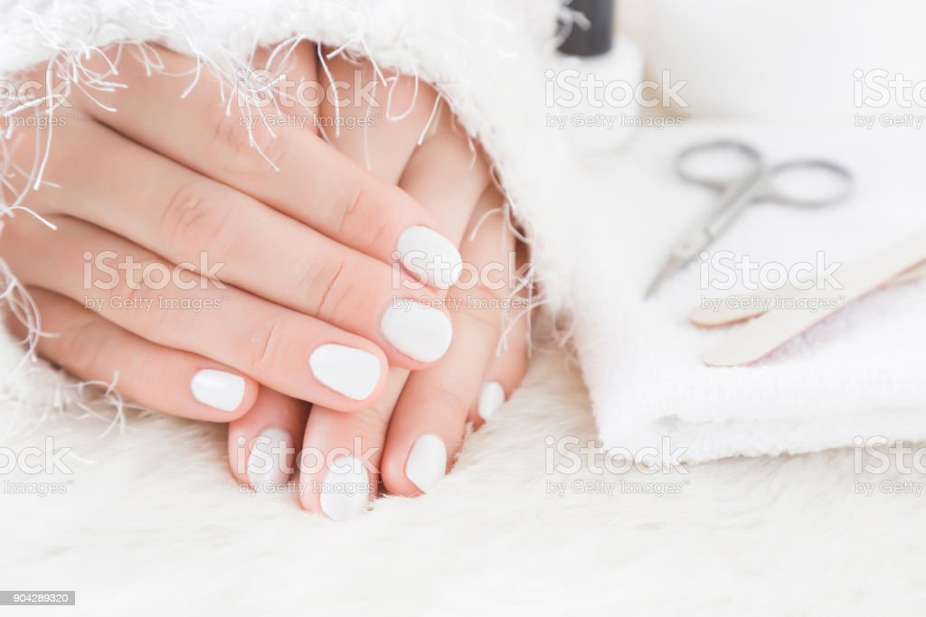 Beautiful groomed woman\'s hands on the fluffy mat. Scissors, nail...