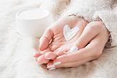 美しい手入れクリーム ジャーふわふわ毛布の上で女性の手を。冬時間のきれいで、柔らかい肌のための保湿クリーム。ハート クリームから作成されました。体が大好きです。ヘルスケアの概念。