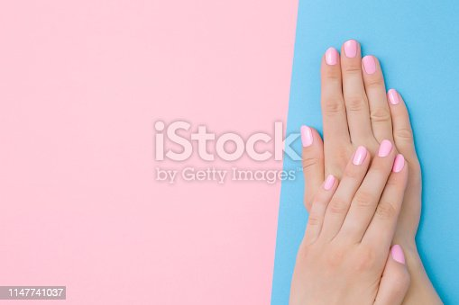 1147741037 istock photo Beautiful groomed woman's hands with pink nails on light pastel blue and pink background. Manicure, pedicure beauty salon concept. Empty place for text, quote or sayings. Top view. Closeup. 1147741037