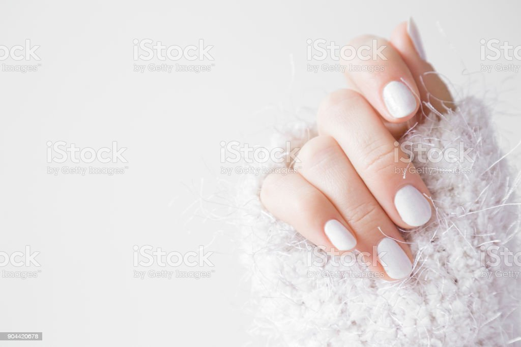 Beautiful groomed woman\'s hands with white nails on the light gray...