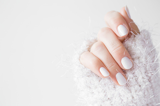 istock Beautiful groomed woman's hands with white nails on the light gray background. Nail varnishing in white color. Manicure, pedicure beauty salon concept. Empty place for text or logo. 904420678