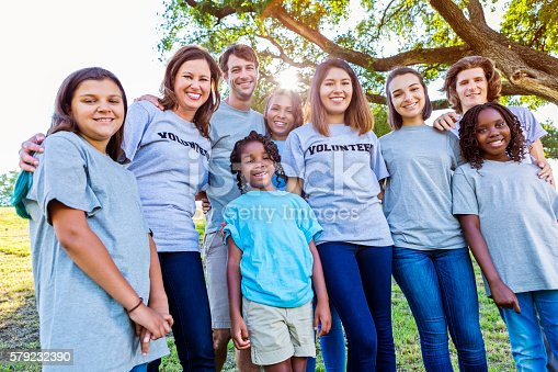 Diverse group of choldren and adult volunteers. They are wearing volunteer t-shirts. They are all smiling at the camera. There is a tree and the sun is coming through the branches in the background.