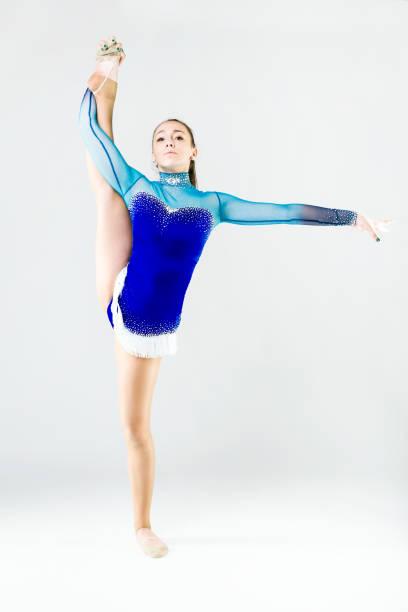 Beautiful gymnast athlete doing exercise. Isolated on white. stock photo
