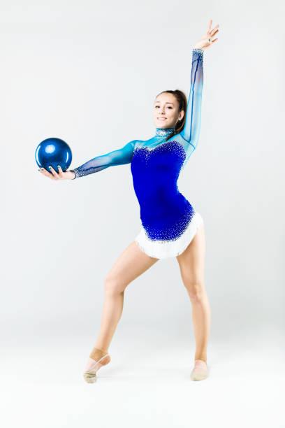 Beautiful gymnast athlete doing exercise with ball. Isolated on white. stock photo