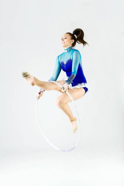 Beautiful gymnast athlete doing exercise with hoop. Isolated on white. stock photo