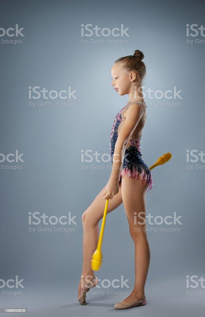 Beautiful gymnast girl in sportswear, rhythmic gymnastics element...