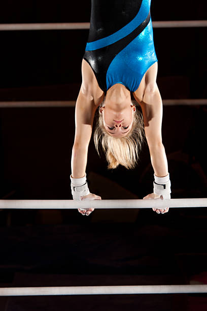 beautiful gymnast pauses in a handstand atop uneven bars - uneven parallel bars stock photos and pictures