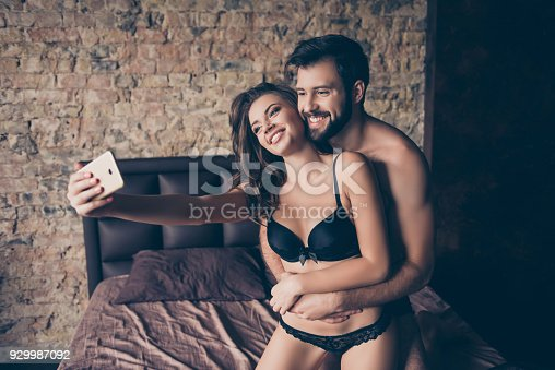 istock Beautiful half naked brunet couple is embracing in bed, lady takes selfie, so tender, romantic, tempting, sensual. True love and feelings, brunet hugs her from back behind, enjoying, laughing 929987092