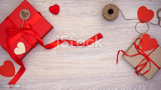 1125461272 istock photo Beautiful hand-made giftboxes with red paper hearts on wooden background present 1125461280