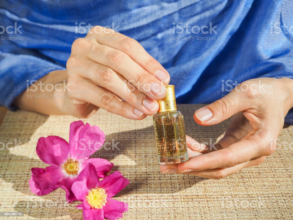 Beautiful hands of a Muslim woman with a perfume. Hands of a woman with perfume. Arab woman opening perfume bottle. royalty-free stock photo