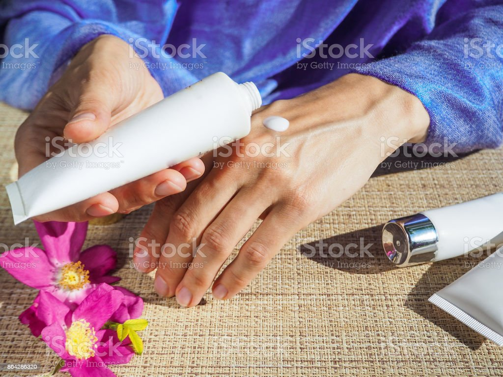 Beautiful hands of a Muslim woman with a perfume. Hands of a woman with perfume. Arab woman opening perfume bottle. stock photo