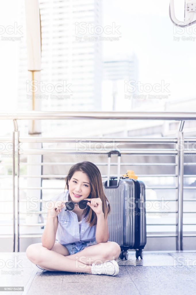 Beautiful happiness young asian girl in casual dress traveling alone at  train station or airport with backpack vintage tone photo concept - Stock  image .